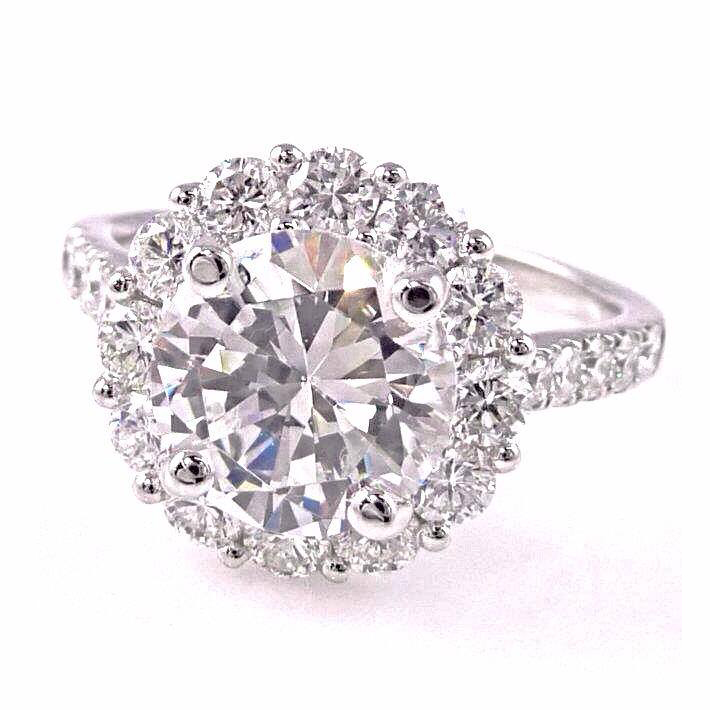 2.89 carat round brilliant cut diamond set into 18k white gold diamond halo setting. Total diamond carat weight: 3.94 ct.