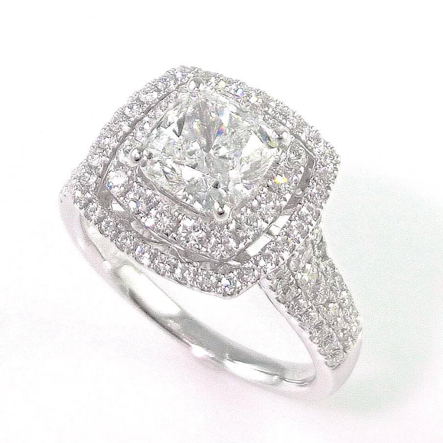 1.78 carat cushion cut diamond set into 18k white gold diamond halo setting. Total diamond carat weight: 2.69 ct
